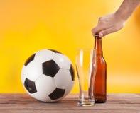 男性手开放瓶在足球玻璃附近的啤酒 免版税库存图片