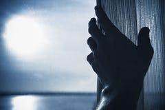 男性手打开窗口的薄纱,被定调子的蓝色 免版税库存图片