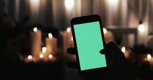 男性手拿着有绿色屏幕的智能手机 行动的少量类型-重击权利和轻拍 在的被点燃的蜡烛 股票录像