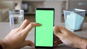 男性手拿着有绿色屏幕色度嘲笑的一个智能手机 股票录像