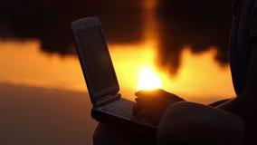 男性手指在个人计算机键盘打印室外在河岸在日落 股票录像