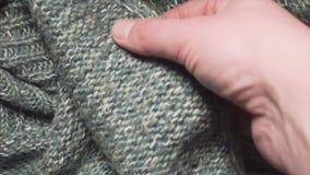 男性手接触在的一件光滑的绿色丙烯酸酯的毛线衣纺织品购物 股票录像