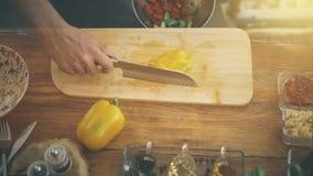 男性手放黄色辣椒粉入碗 库存图片