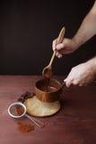 男性手混乱熔化了在平底锅的巧克力漩涡在木背景 免版税库存照片