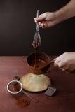 男性手混乱熔化了在平底锅的巧克力漩涡在木背景 库存照片