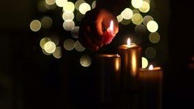 男性手点燃蜡烛 关闭三个灼烧的蜡烛有被弄脏的圣诞灯背景 影视素材