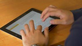 男性手特写镜头使用现代数字式片剂和计算机的在办公室,前面观点的商人递键入的文本 免版税库存图片
