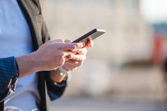 男性手特写镜头在街道上拿着手机户外 使用流动智能手机的人 库存照片
