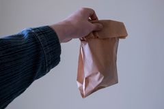 男性手舒展与今后未知的内容的一个纸袋 生态包装食物,拒绝的概念  免版税库存图片