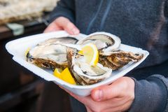 男性手藏品的关闭拿走有新被打开的牡蛎和柠檬切片的食物盘子在街道食物市场,节日,事件上 S 免版税库存图片