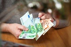 男性手认为欧洲钞票 在100和50欧元的衡量单位的欧洲钞票 免版税库存照片