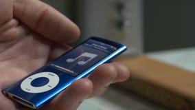 男性手连接耳机到iPod,音乐播放器, MP3播放器 对耳机在妇女的手上 现代 免版税图库摄影