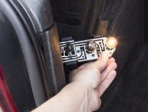 男性手,一个电灯泡的替换在汽车的后方车灯的,特写镜头 库存照片