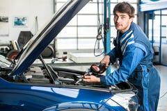 男性技工填装的油到Car& x27里; 在车库的s引擎 免版税库存照片