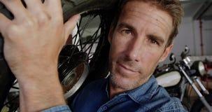 男性技工运载的摩托车在修理车库4k转动 影视素材