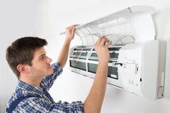 男性技术员清洁空调系统 免版税库存图片
