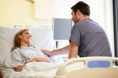 男性护士谈话与女性患者在医房 库存照片