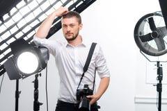 年轻男性摄影师在聚光灯倾斜 免版税图库摄影