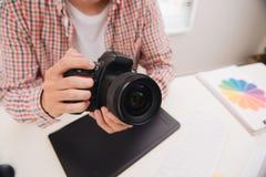 男性摄影师,坐在他的书桌,看对照相机 免版税库存图片