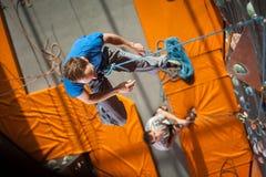 男性摇滚登山人实践的上升在岩石墙壁上户内 免版税图库摄影
