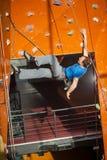 男性摇滚登山人实践的上升在岩石墙壁上户内 免版税库存图片