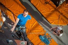 男性摇滚登山人实践的上升在岩石墙壁上户内 库存图片
