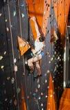 男性摇滚登山人实践的上升在岩石墙壁上户内 库存照片