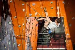 男性摇滚登山人实践的上升在岩石墙壁上户内 免版税库存照片
