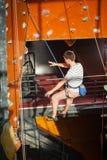 男性摇滚登山人实践的上升在岩石墙壁上户内 图库摄影