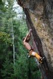 男性攀岩运动员努力到达他的在一个峭壁的下个夹子 极其体育运动 免版税库存图片