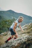 男性攀登山的运动员高年级对山腰 图库摄影