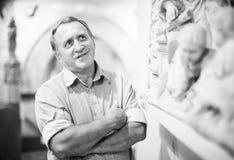 男性收藏家在历史博物馆评估陈列 库存图片