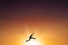 男性收养在空气飞跃在黄昏时间 免版税库存照片