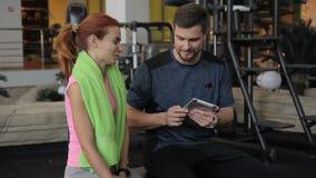 男性教练员计数他的他的片剂的女性客户的结果在健身房 影视素材