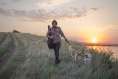 男性旅客步行画象与狗的在峭壁 库存照片
