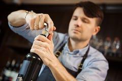 男性有拔塞螺旋的斟酒服务员开放酒瓶 免版税库存照片