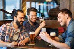 男性朋友用在酒吧的智能手机饮用的啤酒 免版税库存图片