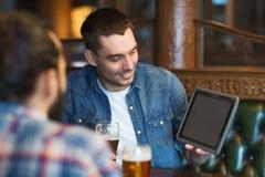 男性朋友用在酒吧的片剂个人计算机饮用的啤酒 图库摄影