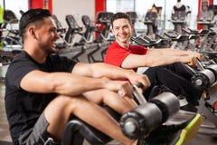 男性朋友谈和获得乐趣在健身房 免版税库存照片