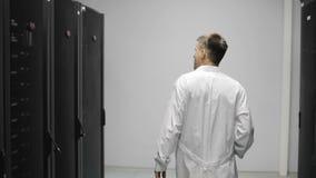 男性服务器工程师通过运作的数据中心的机架服务器充分走 股票录像