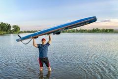 男性桨手和paddleboard在湖岸 免版税图库摄影