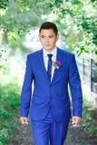 男性模型,在一套蓝色衣服的新郎画象与在绿色叶子中的一朵钮扣眼上插的花在一婚礼之日 免版税库存照片