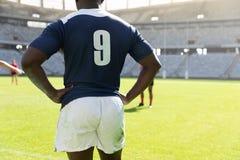男性橄榄球球员身分用在臀部的手在体育场内 库存照片