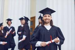 男性毕业生微笑着以大学毕业生为背景 库存照片