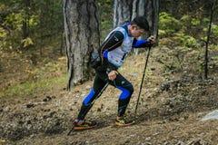 男性沿森林的运动员中年上升落后与北欧走的杆 图库摄影