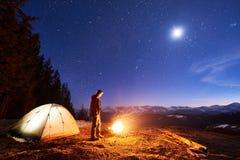 男性游人充分有休息在他的阵营在晚上,在营火和帐篷附近在夜空下星和月亮 免版税库存照片
