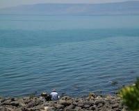 男性游人坐在有齿轮的,读书加利利海一边 免版税库存照片