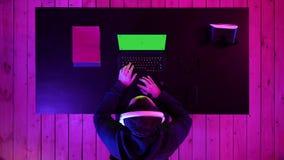 男性游戏玩家打在他的膝上型计算机的比赛 绿色屏幕大模型显示 股票录像