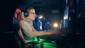 男性游戏玩家播放在俱乐部的一个计算机游戏 股票录像
