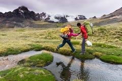 男性爬山者在秘鲁的安地斯帮助伙伴穿过一条河 库存图片